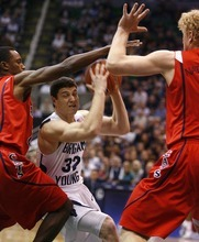 Djamila Grossman  |  The Salt Lake Tribune  Brigham Young University's Jimmer Fredette, 32, is blocked by the University of Arizona's Kyryl Natyazhko, 1, and Kyle Fogg, 21, during a game in Salt Lake City, on Saturday, Dec. 11, 2010. BYU won the game.