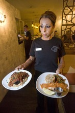 Paul Fraughton  |  The Salt Lake Tribune    Liz Tadros delivers an order of Lebanese moussaka and fresh king salmon recently at Layla Mediterranean Grill and Mezze in Holladay. The Tadros family has transformed their former Confetti's restaurant in name and menu to a gorgeously decorated and sumptuously flavored Mediterranean restaurant.