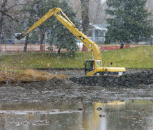 Al Hartmann  |  The Salt Lake Tribune  Cleanup work  continues on the Liberty Park Pond from last Summer's Chevron pipel ine spill.  Backhoes scoop soil from the pond during snowstorm on Monday afternoon.   Signs on the fence surrounding the pond from Chevron say,