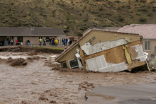 A house in the Beaver Dam Resort area falls into the Beaver Dam Wash in Beaver Dam, Ariz. Tuesday, Dec. 21, 2010. Heavy rains caused the wash to swell over its banks destroying roads and homes along it's path. (AP Photo/Las Vegas Review-Journal, John Locher)