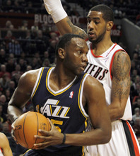 Utah Jazz center Al Jefferson, left, maneuvers against Portland Trail Blazers forward LaMarcus Aldridge during the first half of their NBA basketball game in Portland, Ore., Thursday, Dec. 30, 2010. (AP Photo/Don Ryan)