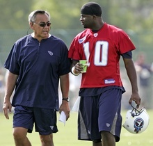 Tennessee Titans offensive coordinator Norm Chow, left, talks with quarterback Vince Young at NFL football training camp July 28, 2007, in Nashville, Tenn. The Titans fired Chow on Tuesday, Jan. 15, 2008, after a season of struggling to score points, although the team reached the playoffs for the first time since 2003. (AP Photo/Mark Humphrey)