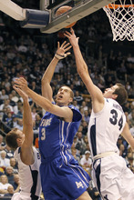 Air Force's Zach Bohannon, center, shoots the ball between BYU's Noah Hartsock, right and Jackson Emery during the first half of an NCAA basketball game in Provo, Saturday, Jan. 8, 2011. BYU beat Air Force 76-66. (AP Photo/George Frey)