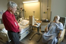 Paul Fraughton  |  The Salt Lake Tribune Bill Kleinschmidt, left, talks with a patient in the University of Utah Medical Center. Bill is a volunteer in the hospital's elder life program (HELP) aiding the patient  with their ensory needs, helping them stay oriented to their surroundings.