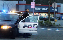 A Bremerton police officer guards the perimeter of the Walmart parking lot in Port Orchard, Wash. where a Washington state sheriff said a shooting left one person dead and two sheriff's deputies wounded Sunday afternoon, Jan. 23, 2011. (AP Photo/The News Tribune, Drew Perine)