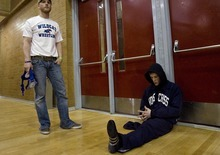 Djamila Grossman  |  The Salt Lake Tribune  Woods Cross High School senior Sasha Prosence takes a moment to himself before he competes in a wrestling tournament at Bountiful High School, Friday, Jan. 28, 2011. His school's assistant coach Johnny Hunt waits to help him get ready.