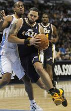 Utah Jazz guard Deron Williams, right, runs around Denver Nuggets guard Arron Afflalo (6) during the first quarter of an NBA basketball game, Friday, Feb. 4, 2011, in Denver. (AP Photo/Barry Gutierrez)