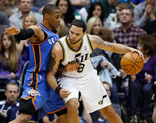 Utah Jazz guard Deron Williams (8) drives along the baseline against Oklahoma City Thunder guard Russell Westbrook (0) during the first half of their NBA basketball game in Salt Lake City, Saturday, Feb. 5, 2011. (AP Photo/Steve C. Wilson)