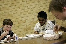 Photo courtesy Ramin Rahimian Kanal Sah, 13, has lunch with classmates Cody Seager, left, and Richard Wilson, during school at Green River High School March 7, 2007. Kanul  joined his parents in India last year and says he misses Green River.