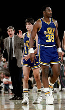 Karl Malone (32) and John Stockton (12) of the Utah Jazz head onto court after meeting with head coach Jerry Sloan against the Atlanta Hawks at the Omni circa 1986 in Atlanta, Georgia. Sloan resigned Thursday, bringing to a stunning end a long career in Utah that included most of his 1,221 career coaching victories and induction into the basketball Hall of Fame.