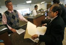 Francisco Kjolseth  |  The Salt Lake Tribune Mexican consulate official Jose Umberto Gutierrez, left, accepts a letter from Raul Lopez-Vargas containing 135 signatures at the Mexican Consulate in Salt Lake City Monday. The petition asks the Mexican president to suspend visas to Mormon missionaries until the LDS Church takes a stronger stand on immigration reform.