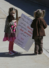 Francisco Kjolseth  |  The Salt Lake Tribune  Leah Lund, 4, left, and her sister Clara, 2, join other home- schooled kids outside of the Provo City Center on Tuesday  to protest a proposal to crack down on truants.