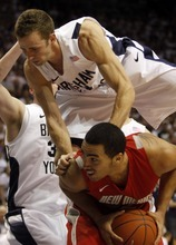 Rick Egan  |  The Salt Lake Tribune  BYU guard Jackson Emery (4) lands on the back of Drew Gordon (32) New Mexico, in Mountain West Basketball action, BYU vs New Mexico in the Marriott Center in Provo, Wednesday, March 2, 2011