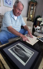 Steve Griffin  |  The Salt Lake Tribune    Bob Phillips looks over photos and original designs for the Spiral Jetty  in his Ogden home Thursday, Feb. 24, 2011.  Phillips was the contractor who built the Spiral Jetty for artist Robert Smithson.