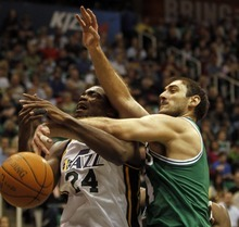 Rick Egan   |  The Salt Lake Tribune  Utah Jazz forward Paul Millsap is fouled by Boston Celtics guard Nenad Krstic on Monday at EnergySolutions Arena in Salt Lake City. The Jazz lost 107-102 before a sell-out crowd after committing defensive lapses down the stretch.