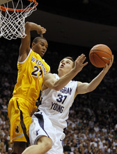 BYU's Kyle Collinsworth, right, shoots past Wyoming's Amath M'Baye during the second half of an NCAA college basketball game in Provo, Utah, Saturday, March 5, 2011. BYU beat Wyoming 102-78 to win the Mountain West Conference Championship. (AP Photo/George Frey)