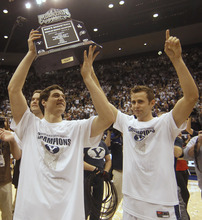 BYU's Jimmer Fredette, left, and Jackson Emery holds holds up the Mountain West Championship trophy after a win against Wyoming at an NCAA college basketball game in Provo, Utah, Saturday, March 5, 2011. BYU beat Wyoming 102-78 to win the Mountain West Conference Championship. (AP Photo/George Frey)