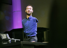 Scott Sommerdorf  |  The Salt Lake Tribune Nick Vujicic speaks from atop a desk before a full house at Mountain View Christian Assembly in Sandy, Sunday, March 13, 2011. Vujicic was born without arms or legs, as a result of a rare disorder called Tetra-amelia. He is now a motivational preacher who speaks on life without limbs, life without limits.