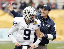 BYU's Jake Heaps (9) celebrates an early touchdown against UTEP with quarterbacks coach Brandon Doman during the first quarter of the New Mexico Bowl NCAA college football game Saturday, Dec. 18, 2010, in Albuquerque, N.M. (AP Photo/Ross D. Franklin)
