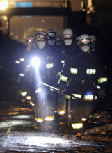Firefighters continues search under the rain at the earthquake and tsunami devastated area Tuesday night, March 15, 2011, in Kesennuma, Miyagi Prefecture, Japan, four days after the disaster. (AP Photo/Kyodo News)