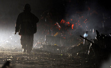 A firefighter continues search under the rain at the earthquake and tsunami devastated area Tuesday night, March 15, 2011, in Kesennuma, Miyagi Prefecture, Japan, four days after the disaster. (AP Photo/Kyodo News)