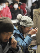 A woman cries while talking on a free pay phone installed for earthquake/tsunami victims in Kesennuma, northern Japan, Wednesday, March 16, 2011, after Friday's earthquake and tsunami. (AP Photo/The Yomiuri Shimbun, Miho Ikeya)