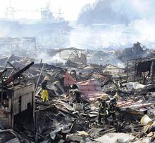 Rescuers conduct search operation amidst smoldering debris in Kesennuma, northern Japan Monday, March 14, 2011 following Friday's massive earthquake and the ensuing tsunami. (AP Photo/Yomiuri Shimbun, Miho Ikeya)