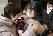A woman talks to Yuki Yamazaki, 3, held by his mother Yoshiko, when he meets his mother first time in four days in Yamada, northern Japan, Tuesday, March 15, 2011, after Friday's powerful earthquake-triggered tsunami hit the country's east coast. The tsunami also engulfed their home. (AP Photo/Kyodo News)