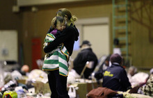 A woman holds her child at a shelter after being evacuated from areas around the Fukushima nuclear facilities damaged by last week's major earthquake and following tsunami, Wednesday, March 16, 2011, in Fukushima city, Fukushima prefecture, Japan. (AP Photo/Wally Santana)
