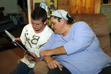 In this Jan. 26, 2011 photo, Gregory Roskilly, 15, reads to his mother Sandra Roskilly at their home in Denver. Gregory, who has autism and mood disorder, left the Colorado Mental Health Institute at Fort Logan last year when it closed its children's ward because of budget cuts. He now lives at home, where his mother has moved in to help care for him, but she fears Gregory is getting worse without residential treatment. (AP Photo/Ed Andrieski)