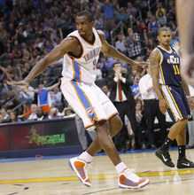 Oklahoma City Thunder forward Serge Ibaka gestures after dunking against the Utah Jazz in the fourth quarter of an NBA basketball game in Oklahoma City, Wednesday, March 23, 2011. Jazz guard Earl Watson is at right. Oklahoma City won 106-94. (AP Photo/Sue Ogrocki)