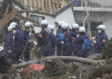 Police officers and others search for missing persons in the March 11 earthquake and tsunami-destroyed city of Kamaishi, northern Japan Saturday, March 26, 2011. (AP Photo/Yomiuri Shimbun,