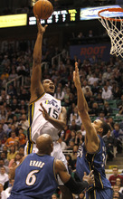 Rick Egan   |  The Salt Lake Tribune  Utah Jazz guard Derrick Favors (15)  scores over Maurice Evans, (6) and Washington Wizards center JaVale McGee (34)  in NBA action Utah vs Washington, in Salt Lake City, Monday, March 28, 2011. Wall was held scoreless in the second half of regulation play.