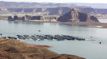 Boaters are dwarfed by the sandstone walls of Lake Powell. Tribune file photo