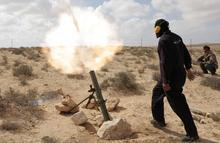 A Libyan rebel shells pro Gadhafi forces with mortar fire, along the front line outside the eastern town of Brega, Libya Thursday, March 31, 2011. Libya conceded Thursday that Foreign Minister Moussa Koussa had resigned but claimed that it was a personal decision driven by health problems, not a sign that the embattled regime is cracking at the highest levels. (AP Photo/Nasser Nasser)
