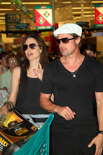 **CORRECTS LOCATION OF TWINS BIRTH TO NICE FRANCE NOT NAMIBIA** In this photo taken Thursday, Dec. 23, 2010 Angelina Jolie and Brad Pitt do Christmas shopping at a mall in Windhoek, Namibia . Jolie gave birth to twins two years ago in Nice, France. (AP Photo/Francois Poolman)