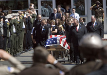 Steve Griffin  |  The Salt Lake Tribune Law enforcement officers salute as Shawna Harris and her daughters, Kristina and Kirsten follow the casket of her husband Kane County sheriff's Deputy Brian Harris as it is carried to the hearse outside Valley High School during funeral services  in Orderville, UT  Friday, September 3, 2010.