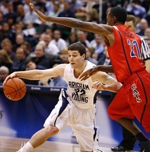 Djamila Grossman  |  The Salt Lake Tribune  Jimmer Fredette drives against Arizona's Kyle Fogg on Dec. 11.