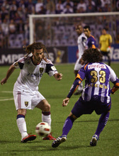 U.S. Real Salt Lake's Kyle Beckerman, left, kicks the ball as Costa Rica's Deportivo Saprisa Luis Diego Cordero looks on during a CONCACAF Champions League soccer game in San Jose, Costa Rica, Tuesday April 5, 2011. (AP Photo/Ronald Reyes)