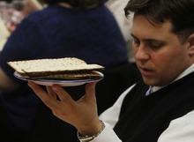 Rick Egan   |  The Salt Lake Tribune  A prayer is said as Justin Jones holds up  the plate of matzah  during a Seder service at the WIlkinson Center at Brigham Young University, Saturday, April 9, 2011.  For nearly 40 years, BYU professor Victor L. Ludlow,  a specialist in Jewish studies, has been conducting the celebrations at BYU.