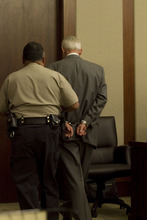 Adam Metcalf  |  Associated Press pool William Hammons is escorted out of a St. George courtroom. He was convicted in February on seven counts of securities fraud related to his involvement in VesCor was ordered Friday to spend a year in the Washington County Jail and to pay restitution.