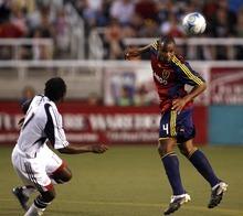 Jamison Olave, right, tips the ball for Real Salt Lake as Khel Dube defends for the Revolution on Saturday at Rice-Eccles Stadium. Rick Egan/The Salt Lake Tribune 6/21/08