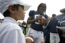 Francisco Kjolseth  |  The Salt Lake Tribune Aggie fan Desmond Phillips, 8, gets his football signed by Travis Reynolds as following Utah State's Spring football game on Saturday, April 23, 2011, at Romney Stadium in Logan in front of the Aggie fans.