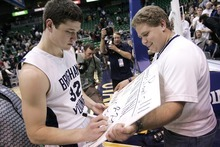 Djamila Grossman  |  The Salt Lake Tribune  Jimmer Fredette gives an autograph to fan Trent Boulter after a game against the University of Arizona in Salt Lake City, on Dec. 11, 2010.