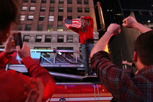 Dustin Fredrickson, of New York, center, holds up an American flag as he stands on a fire truck amongst those gathered in New York's Times Square reacting to the news of Osama Bin Laden's death early Monday morning May 2, 2011. (AP Photo/Tina Fineberg)