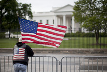 Dan Parker from Shamokin, Pennsylvania, stands outside the White House with a U.S. flag in Washington, D.C., U.S., on Monday, May 2, 2011. Al-Qaeda leader Osama bin Laden, the architect of a radical Islamist movement that killed almost 3,000 people on Sept. 11, 2001 and recast global security and politics, was killed in Pakistan yesterday after a decade on the run in a firefight with a team of U.S. operatives who raided the compound where he had been hiding. Andrew Harrer/Bloomberg