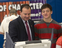 Al Hartmann  |  The Salt Lake Tribune Mike Lee votes at Alpine Elementary School. His son James, alongside the voting booth, watches.