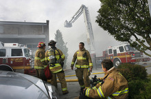 Scott Sommerdorf  |  The Salt Lake Tribune Fire crews work in shifts - some rest while others fight the four alarm fire at an unoccupied building near 600 West between 200 and 300 South across from the Intermodal Hub, Saturday, May 14, 2011.