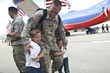 CHRIS DETRICK   The Salt Lake Tribune  Staff Sgt. Kevin Lowe hugs his sons Hunter, 6, and Tracer, 4, as he arrives at the Utah Air National Guard Base Saturday morning. About 100 Soldiers of the Utah National Guard's Group Support Company, 19th Special Forces Group (Airborne), returned to Utah from their 12-month deployment to Iraq.