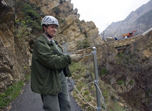 Al Hartmann  |  The Salt Lake Tribune Timpanogos Cave National National Monument maintenance worker Ranae Brown threads steel cable between posts to construct a fence along an exposed part of the trail to the cave in American Fork Canyon.